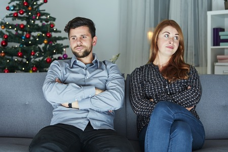christmas spending: young modern couple is irritated of christmas with christmas tree in background