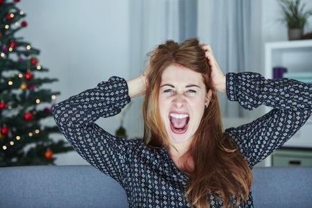 going crazy: young girl screams because of bad christmas stress Stock Photo
