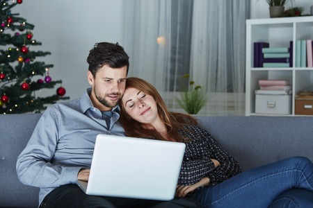 young tree: happy young couple use or watch something on laptop pc for christmas on sofa Stock Photo