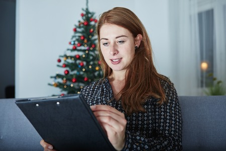 wishlist: young happy woman think about christmas wih list on sofa in front of christmas tree.