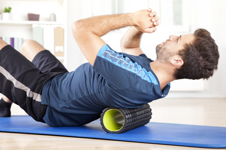 roller: Handsome Healthy Guy Doing an Exercise on a Mat with Foam Roller on his Upper Back
