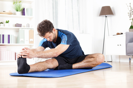 Handsome Young Man Doing Hamstring Stretch Exercise on Top of a Mat at Home.