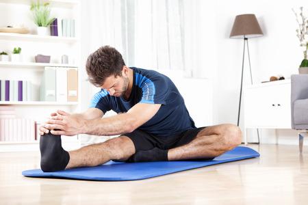 Gut aussehend junger Mann tun Hamstring Stretch-Übung auf einem Matte zu Hause. Standard-Bild
