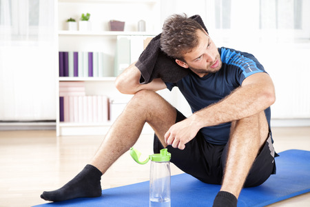 Handsome Athletic Man Wiping his Head with Towel While Resting After his Indoor Exercise At Home, Looking to the Right of the Frame. Standard-Bild