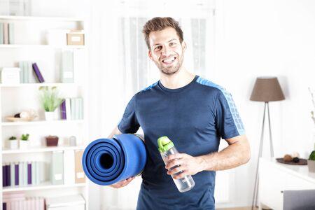 Half body shot van een knappe fit man met een opgerolde mat en een fles water na het doen van een indoor oefening, lachend naar de camera.