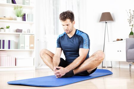 ejercicio aeróbico: Apuesto hombre atlético que hace sentado aductor del estiramiento del ejercicio en el hogar