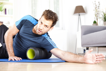 Handsome Young Guy Lying on his Side with Foam Roller Below his Armpit, Looking at the Camera. Stock Photo