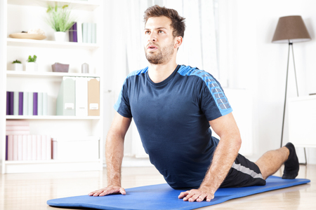 Fit Young Man doet zijn dagelijkse press-up oefening op een fitness mat thuis alleen.