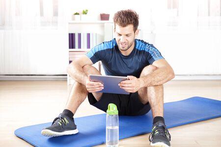 hombre deportista: Aptos hombre joven que se sienta en su estera y usando su ordenador de la tablilla Después de que hace un ejercicio físico interior. Foto de archivo