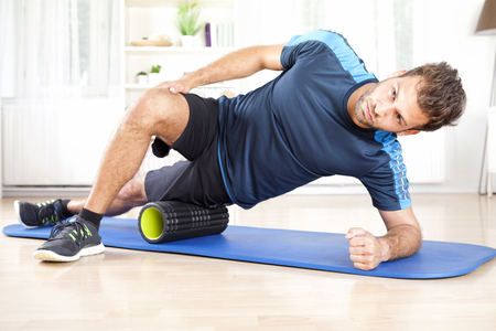 his: Handsome Athletic Young Man Doing Side Planking with Foam Roller on his Thigh.