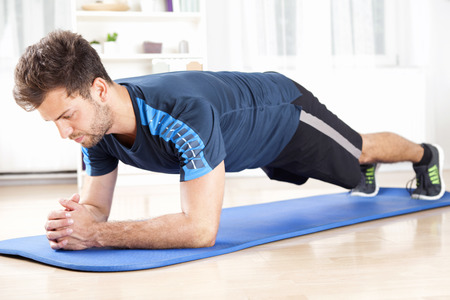 Full Length Shot of a Fit Young Man Performing Planking Exercise on a Mat While Facing the Floor. Stockfoto