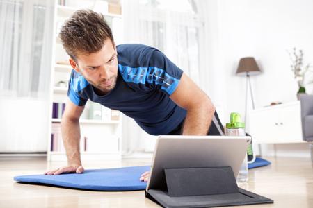 Hombre joven atlético que hace un ejercicio de adoquín en casa mientras ve la película en su Tablet PC. Foto de archivo