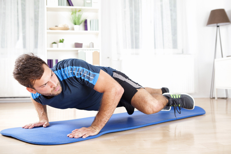 planking: Attractive Fit Young Man Planking on an Exercise Mat While Lifting One Leg and Looking to the Right. Stock Photo