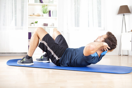 Athletic Young Man Doing Indoor sit Ups Exercise for Abdomen on Top of a Mat at Home. Standard-Bild