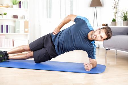 カメラを見ながらマットの上室内側板運動をして健康的なゴージャスな男。