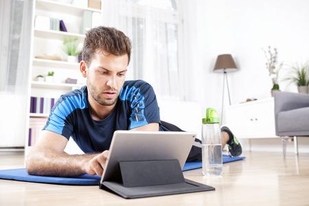 Knappe Jonge Kerel Met behulp van zijn tablet-computer tijdens Liggend op zijn Fitness Mat na het doen van zijn huis Lichamelijke oefening routine. Stockfoto