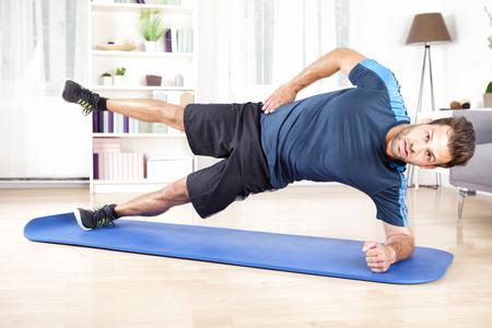 Volledige lengte shot van een knappe atletische man doet Side Plank Oefening met één been in de lucht, op zoek naar de camera.