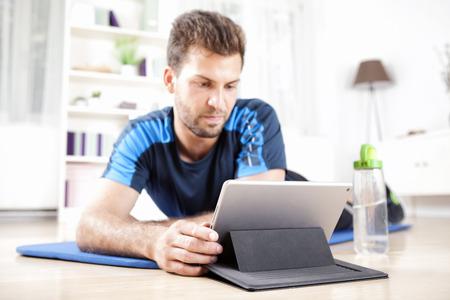 Fit jonge man liggend op zijn Fitnessmat Terwijl Met behulp van zijn tablet-computer na het doen van zijn training.