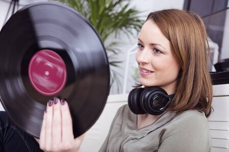 brown haired girl: Attractive brown haired girl sitting smiling with headphones around her necking looking at a record in her hand