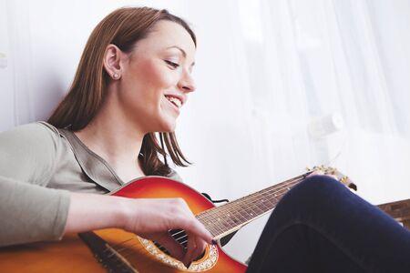 Aantrekkelijke jonge vrouwenzitting die op de vloer speelmuziek op haar gitaar glimlachen