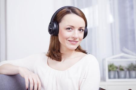 Mooi bruin haired meisje met een koptelefoon op zoek lachend in de camera Stockfoto