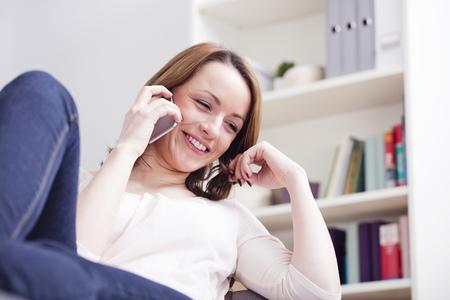 Mooie jonge bruine haired vrouw chatten lacht naar iemand met haar smartphone