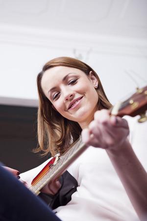 Mooi bruin haird meisje met gitaar in haar handen afspelen van een nummer genieten van haar tijd Stockfoto