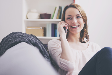 Pretty lachende jonge bruine haired meisje zittend op de bank en praten met haar smartphone