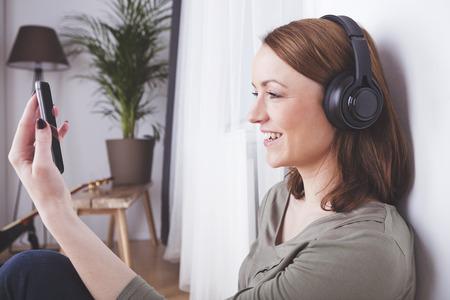 Aantrekkelijke bruine haired vrouw met een koptelefoon houdt glimlachen terwijl het hebben van een video-oproep  het nemen van selfie