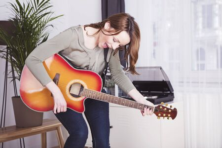 jamming: Cheeky young woman with long brown hair jamming with her with guitar dancing around