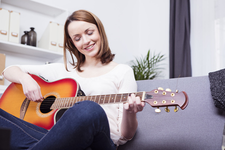 brown haired girl: Happy brown haired girl sitting smiling on sofa having a guitar on her crossed legs playing some records