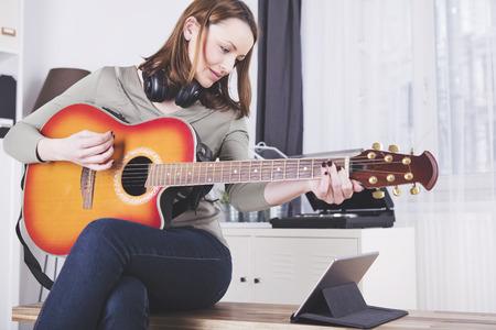 Geconcentreerd bruine haren meisje met hoofdtelefoons rond haar hals spelen een aantal records op gitaar, terwijl het gebruik van een tablet
