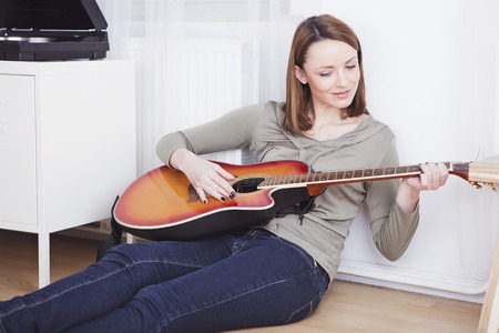 brown haired girl: Beautiful brown haired girl casual dressed relaxing on the floor of living room while playing a song on guitar next to a record player