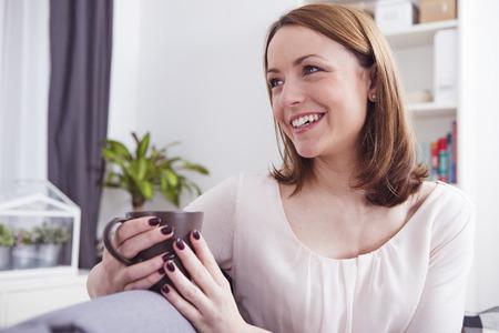 Brutaal jong meisje zit ontspannen op een bank en genieten van haar warme mok koffie of thee Stockfoto