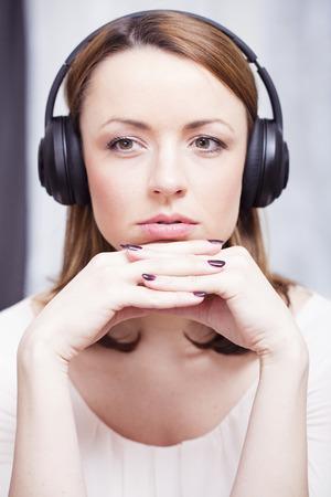 Peinzend bruin haired meisje luisteren naar muziek met haar koptelefoon zetten haar handen gekruist onder haar kin