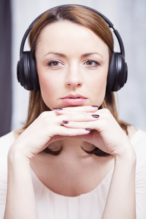 brown haired girl: Pensive brown haired girl listening to music with her headphones putting her hands crossed under her chin Stock Photo