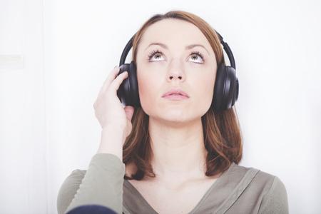 Peinzend bruin haired meisje gekleed casual vergadering luisteren naar muziek tijdens het kijken naar boven Stockfoto