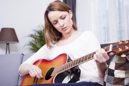 Aantrekkelijk bruine haren meisje spelen geconcentreerd een aantal records op gitaar zittend op de bank in de woonkamer