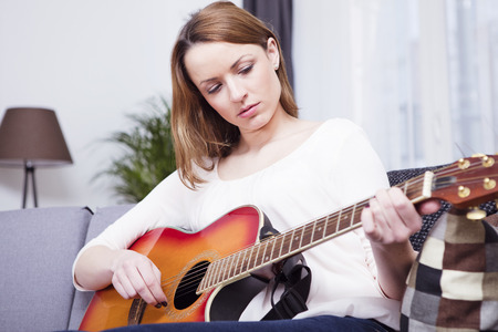 brown haired girl: Attractive brown haired girl playing concentrated some records on guitar while sitting on sofa in living room Stock Photo