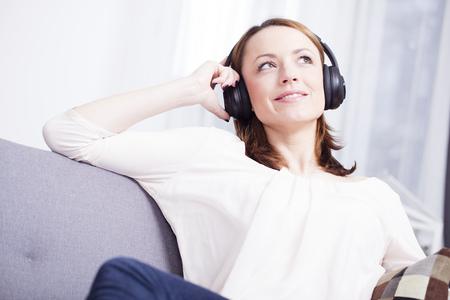 Aantrekkelijk jong meisje geniet van het luisteren naar muziek met een koptelefoon op terwijl het zitten lui op de bank