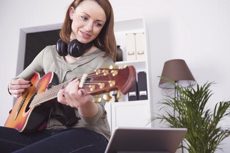 Aantrekkelijk gelukkig jong meisje met lang bruin haar spelen muziek op gitaar tijdens het gebruik van tablet