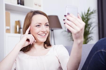 Gelukkig brutale jonge bruine haired meisje met een video-chat of het nemen van een selfie smiling op de bank Stockfoto