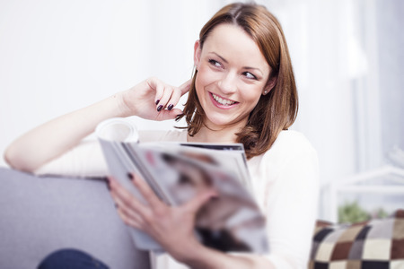 fashion magazine: Pretty young brown haired girl sitting smiling on couch enjoying reading a fashion magazine