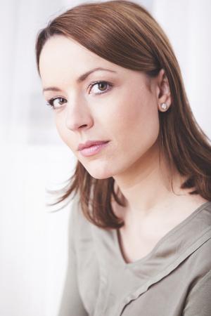 Aantrekkelijke bruine haren casual geklede vrouw lachend in de camera Stockfoto