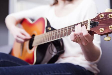 Mooie knappe vrouw playling een aantal records op gitaar, close-up