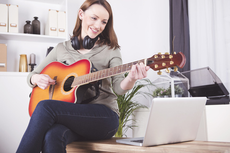 brown haired: Happy smiling brown haired woman casual dressed playing records on guitar supported by laptop
