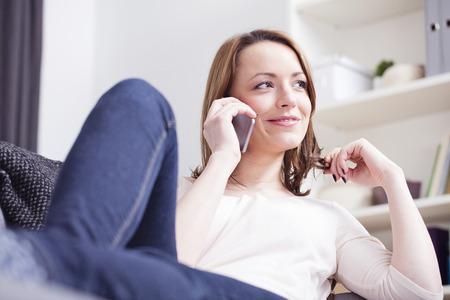 Relaxing bruine haired meisje chatten met iemand met haar smartphone wikkelen haar rond haar vinger