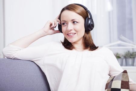 Aantrekkelijke gelukkige bruine haired vrouw te genieten van het luisteren naar muziek met een koptelefoon op haar comfortabele sofa