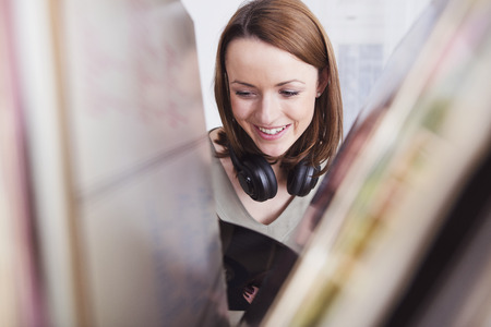 brown haired girl: Happy brown haired girl with headphones around her neck looking on a record in her hand