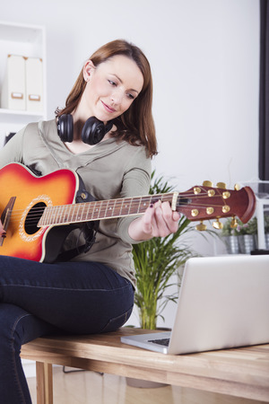 brown haired girl: Pretty smiling brown haired girl sitting on desk playing some records on guitar while using laptop for support